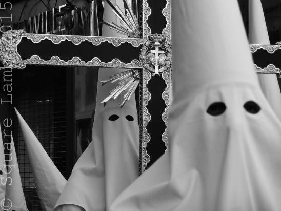 """No, not the Ku Klux Klan. This is the traditional religious Easter costume worn in the processions around the city during Semana Santa - the week leading up to Easter. The participants are called """"Nazarenos"""" and they wear the hoods to symbolise shame at the sins they have committed. The processions are a solemn and serious affair, many Nazarenos march barefoot for hours on end, and are usually accompanied by drums and brass instruments, although some processions are silent. Everything changes on Easter day when the Nazarenos remove the hoods and parade through the streets smiling and throwing flowers to the crowds."""