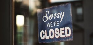 sorry we are closed sign hanging in a doorway
