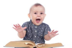 Little excited baby sitting with a book