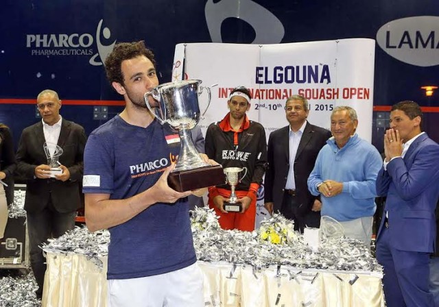 El Gouna champion Ramy Ashour holds the trophy as Mohamed Elshorbagy looks on