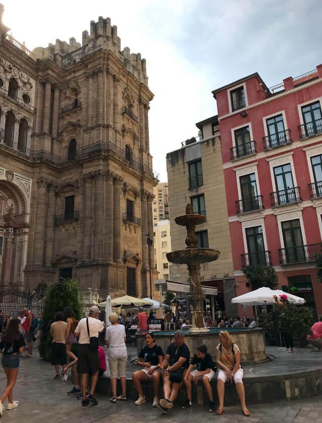 Turisti seduti attorno alla fontana davanti alla Cattedrale di Malaga