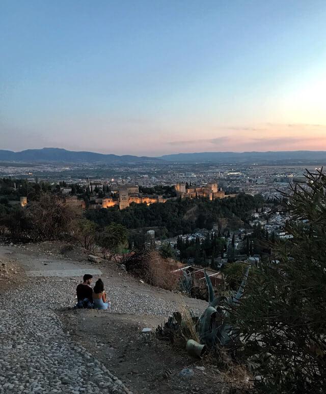 Coppia guarda il tramonto sull'Alhambra dal Mirador de San Miguel Alto