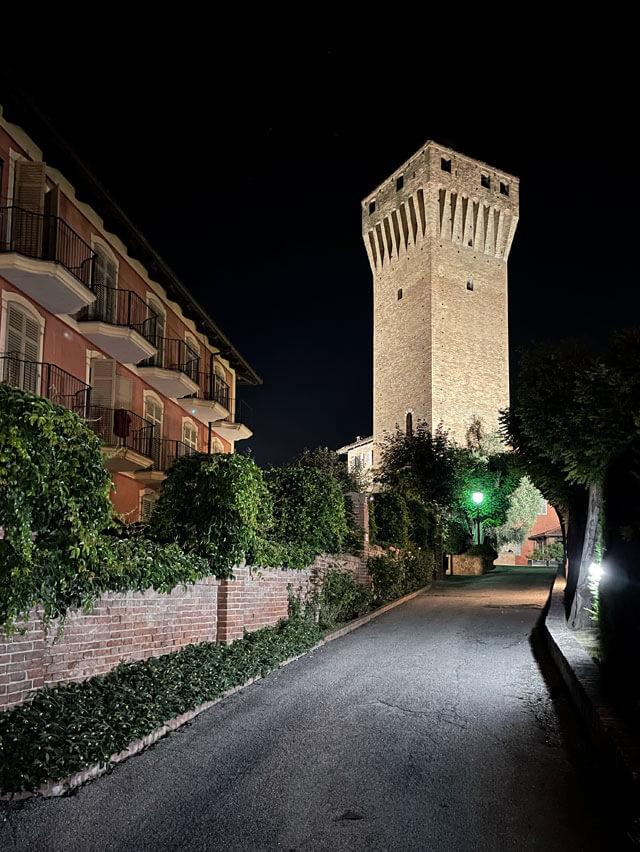 L'Hotel Castello Santa Vittoria di notte con la torre viscontea illuminata