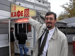 "Aleksandr Belov happily pointing at Kafe 88.  In Nazi slang, 88 stands for ""Heil Hitler."""