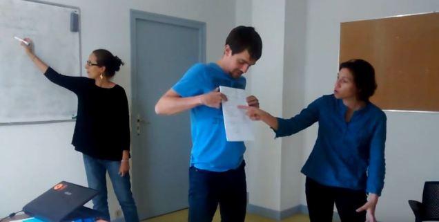 Un groupe de trois personnes raconte son interface en s'aidant de schéma au tableau