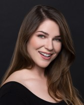 Actress headshot of smiling brunette woman in black dress.
