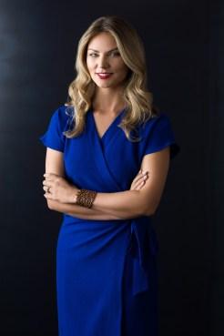 Woman in blue dress half body headshot