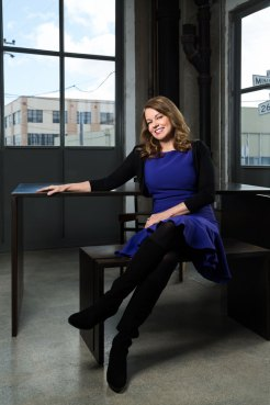 Portrait of woman executive sitting at a table wearing a blue dress.