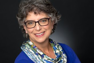 Headshot of woman in blue with glasses