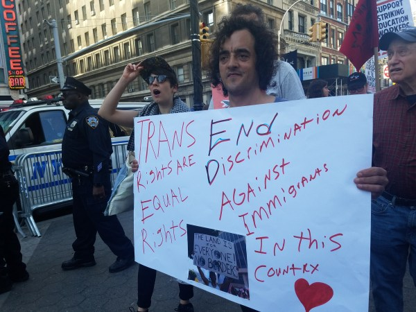 """Movement Building Team member Stephanie at May Day rally holding up a sign taht reads """"Trans Rights are Equal Rights. End Discrimination Against Immigrants in this Country""""."""