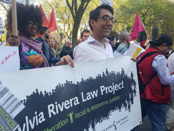 Carlos, SRLP's Direct Services Team intern, marching with SRLP. Carlos is holding up a banner with SRLP's name.