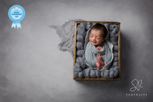 Newborn photography Leicester baby smiling in wooden crate with grey background