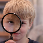 Photo of a child looking through magnifying glass.