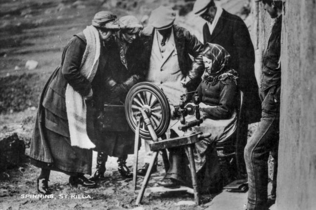 Photograph of curious tourists crowding around a St Kildan woman spinning