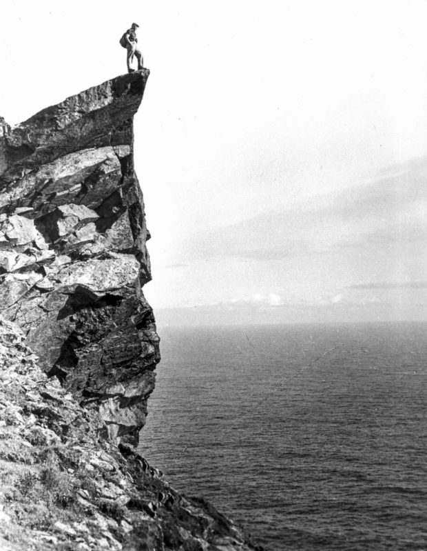 Glass plate negative of a man on the Lover's Stone, Hirta (St Kilda's main island)
