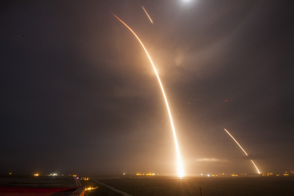 Taken from the top of Kennedy Space Center's iconic Vehicle Assembly Building, this long exposure photo shows the Falcon 9 streaking into space from the Complex 40 launch pad, then returning to Earth nearby at Landing Zone 1 with the light from the re-entry burn and landing burn appearing as streaks. Photo credit: SpaceX