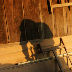 DALAT VIETNAM- JAN 24: Carpenter saw wood by power saw at home he working with concentration his shadow reflect on the wall of wooden house Viet Nam Jan 24 2014