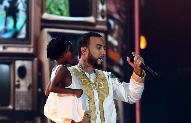French Montana performing on stage holding a kid