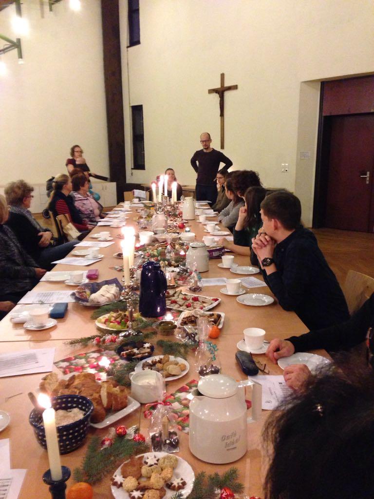 Chormitglieder sitzen um einen reich gedeckten Tisch im Gemeidnesaal von Sankt Martin