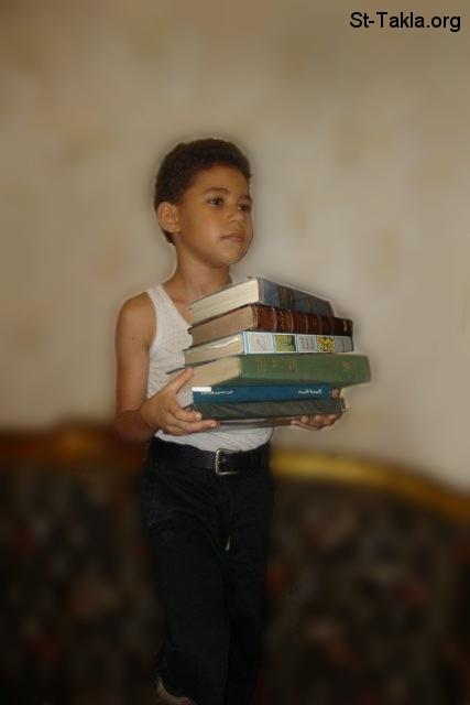 St-Takla.org Image: A boy holding books صورة في موقع الأنبا تكلا: طفل يحمل كتب