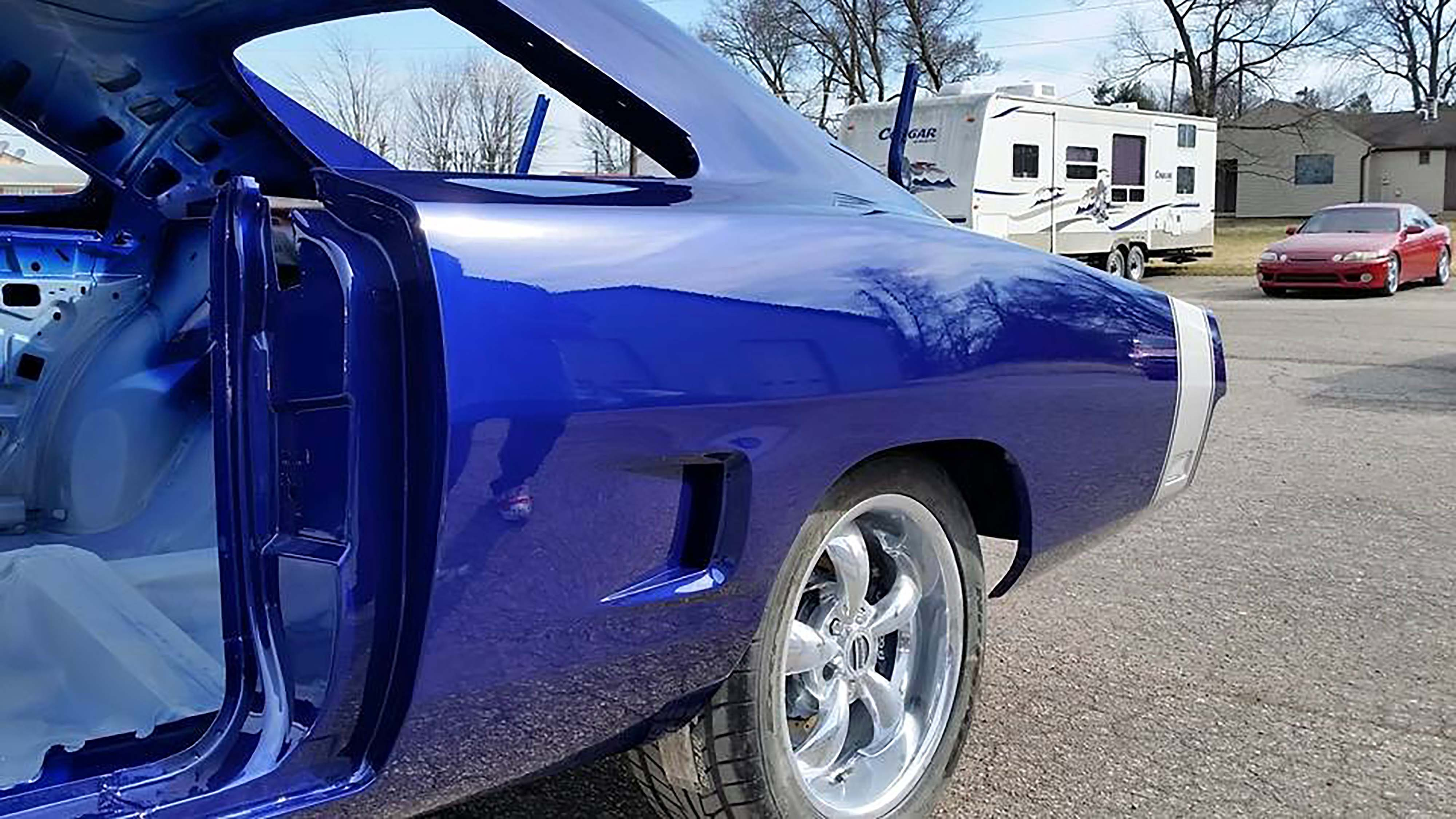 """We threw this little gem in here to visually explain why we bailed on having a logo or symbol in the butt stripe. Remember that we grafted scoops from a 1970 GTX onto the rear quarters of our Charger to create functional cooling ducts for the rear brakes. We felt that was enough """"accent"""" for the rear of the car."""