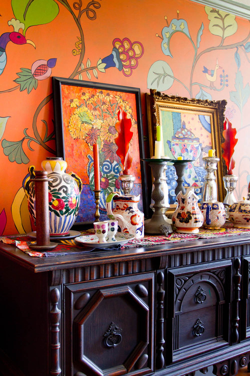 Sala com parede estampada e florida, quadros e móvel antigo de família repaginado