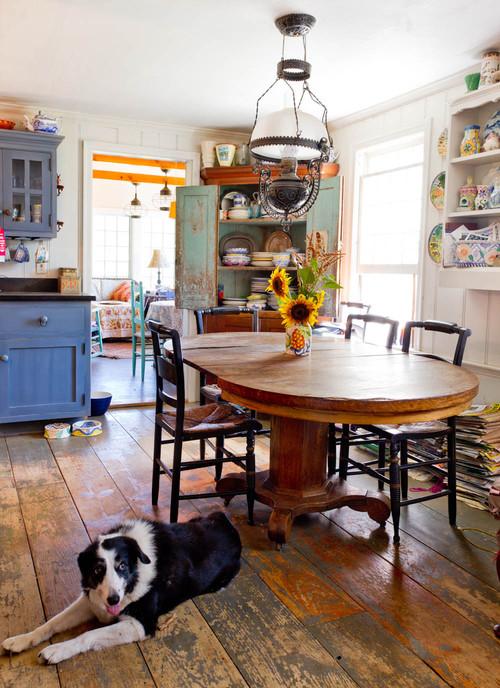 Cozinha rústica com móveis de madeira coloridos, piso de madeira de demolição, luminária de ferro fundido antiga, mesa de madeira antiga