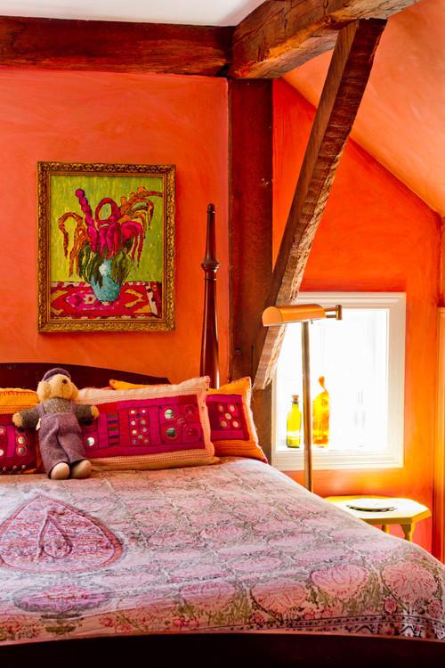 quarto com parede laranja de patna ganha ar rústico com madeira aparente no teto