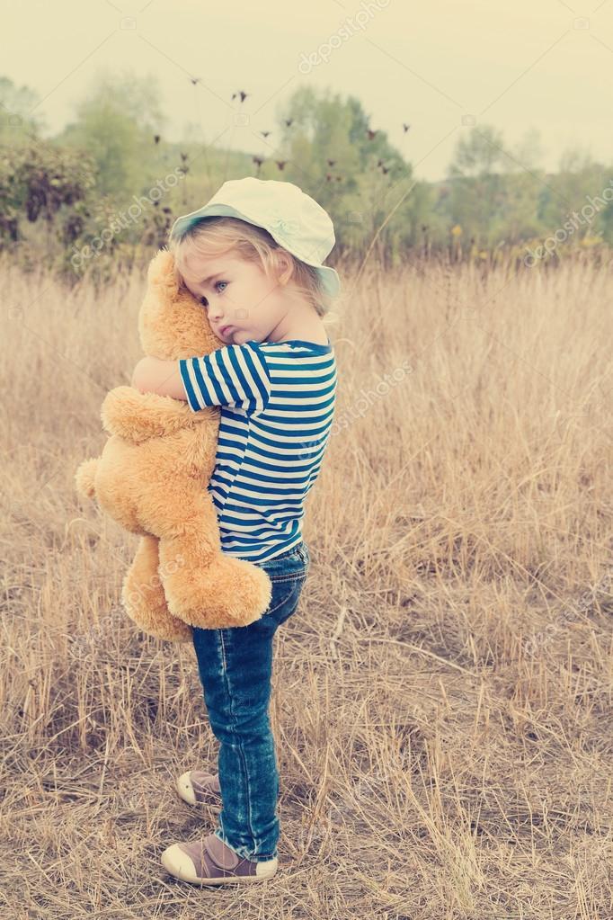 Cute Little Girl Hugging A Big Teddy Bear Stock Photo