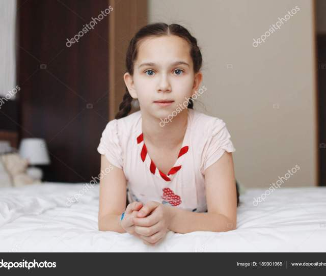 Young Cute Teen Girl Lies In Bed With White Clothes And Looks At Camera Stock