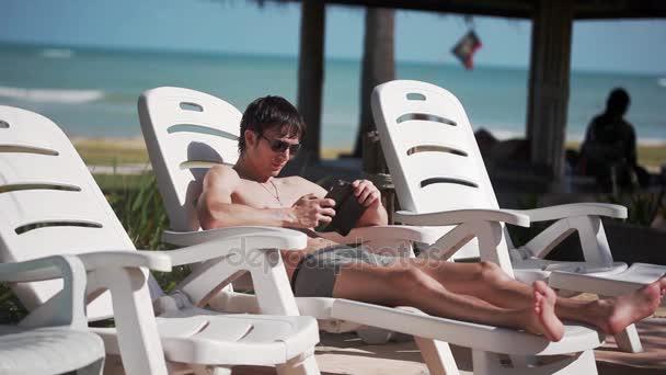 jeune homme lunettes de soleil mains texto sms de la piscine en position couchee sur