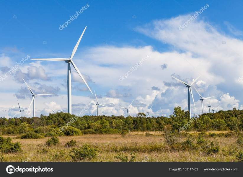 Windmills wind turbines for electric power production in green field     Windmills wind turbines for electric power production in green field      Stock Photo