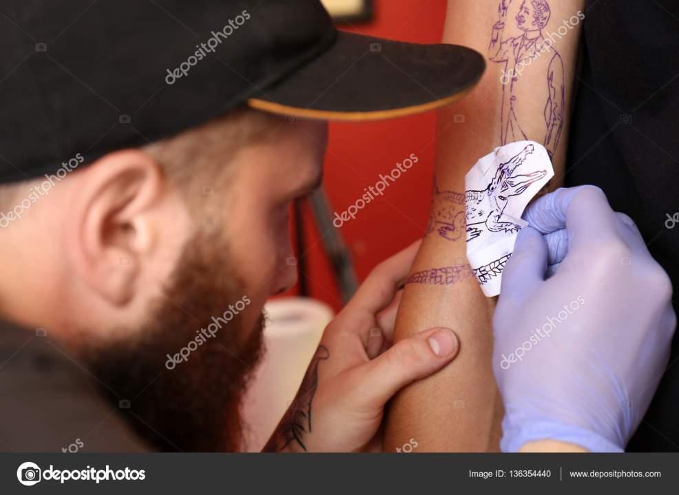 тату мастер студии применяя эскиз мужской руку вид вблизи стоковое