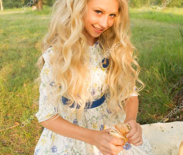 Beautiful Charming Long Curly Blonde Hair Teenage Girl Wearing A Long Light Dress Outdoors On A Picnic Sitting Next To A Basket Full Of Food Drinks A Milk