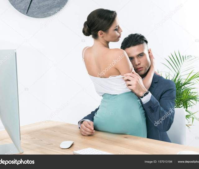 Businesspeople Hugging In Foreplay At Workplace Stock Photo