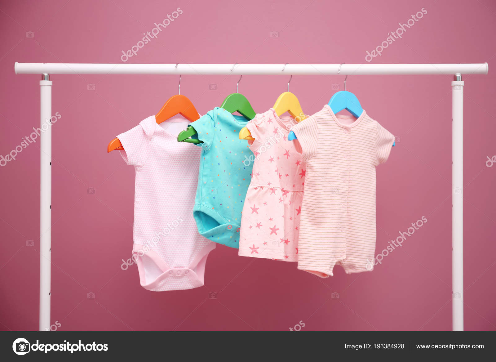 baby clothes hanging on rack against color background stock photo image by c newafrica 193384928