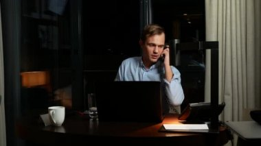 Handsome young businessman sitting at desk in office     Stock Video     Young businessman talking on landline phone  sitting at desk in office at  night  front