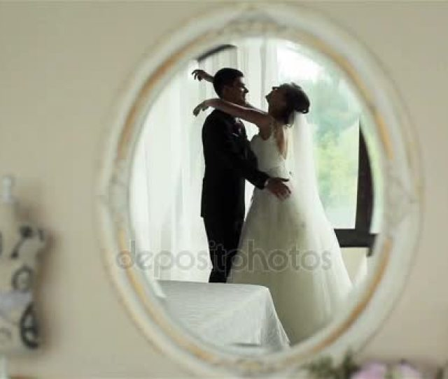 Happy Newly Wedded Couple Bride And Groom Embrace And Kiss Feeling Happy Reflected In Mirror On Wall Of First Night