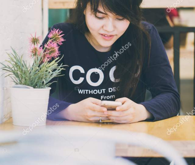Asian Teen Women Using Mobile Smartphone And Smile Happiness Sitting In The Cafe Looking At Screen Photo By Coffeekai