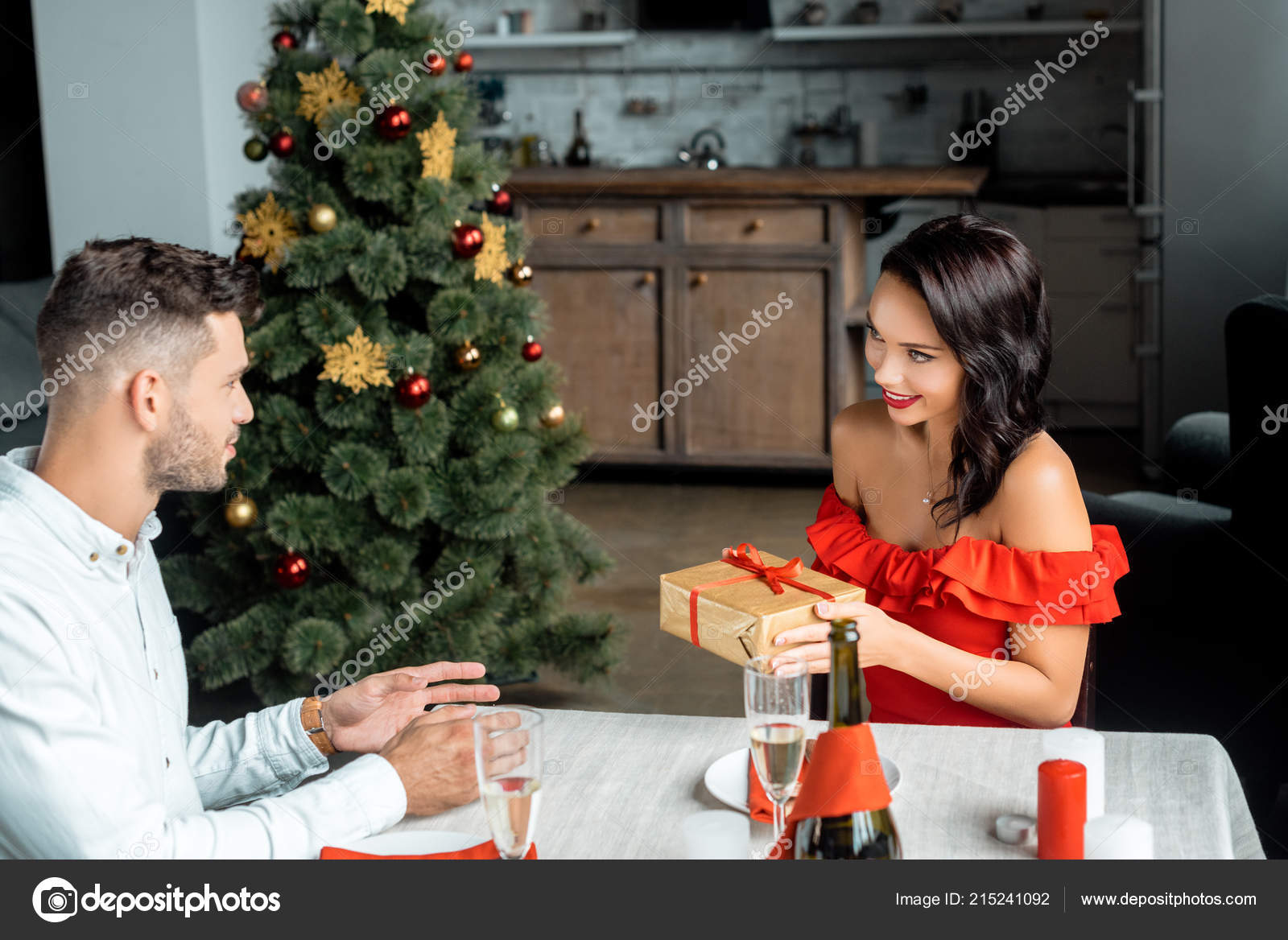 Attractive Young Woman Gifting Christmas Present Boyfriend Sitting Served Table Stock Photo C Igorvetushko 215241092