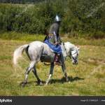 Reconstruction Medieval Armored Knight On White Horse From Fantasy Equestrian Soldier In Historical Costume Reenactor Is In The Summer Stock Photo C Valyalkin 216445224