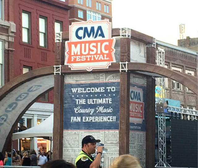 Photo Of Welcome Signage And Cop Staying Hydrated In The Heat For Cma Music Festival In