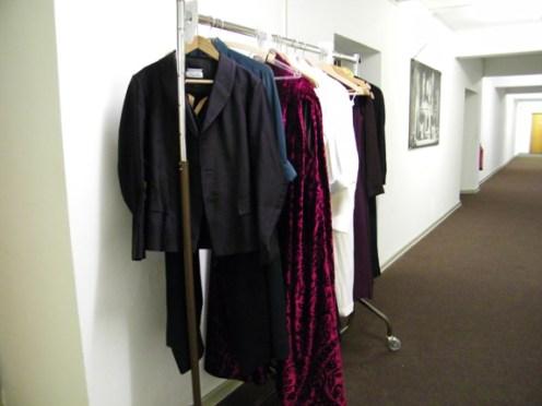 Garderobenstange mit Kostümen im Flur.