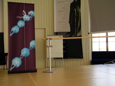 Im Gläsernen Foyer steht ein Aufsteller mit dem Motiv unserer Jahresvorschau 12/13 auf der Bühne.