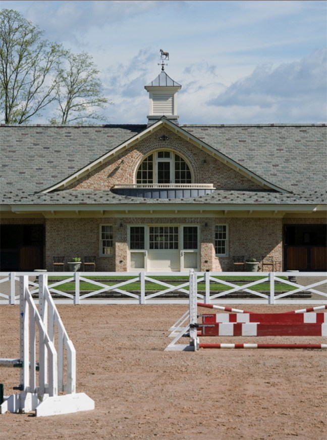 Brick stable and jumps set up in the outdoor riding arena