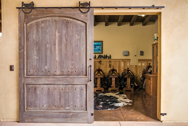 A stunning tack room with western saddles and cowhide