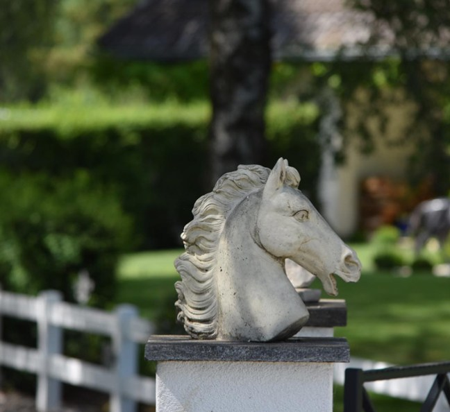 horse head statues on the fence