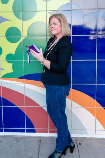 Woman with cell phone posing for a photograph in front of a colorful mural
