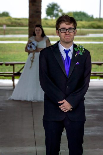 Groom waits as his bride sneaks up behind him for a first look.