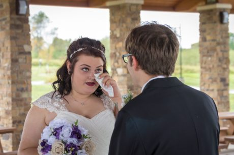 Bride dries her tears after seeing her groom for the first time.